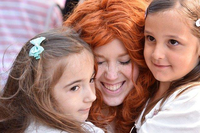 žena objímá dvě holky, mají hlavy u sebe, má pihy a zrzavé vlasy